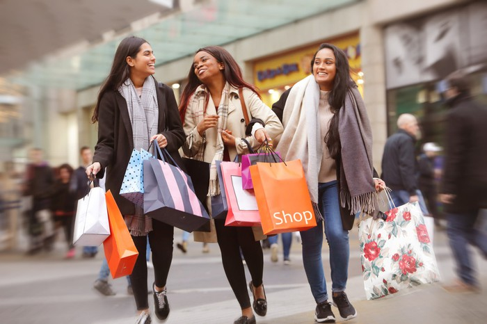 Three people holding shopping bags and walking through a mall.
