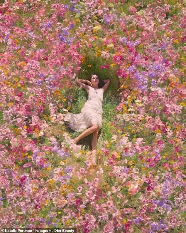 Dreamy:She is also seen in a beige sun dress for a brief time as she lays in a field of pink, purple and yellow wild flowers